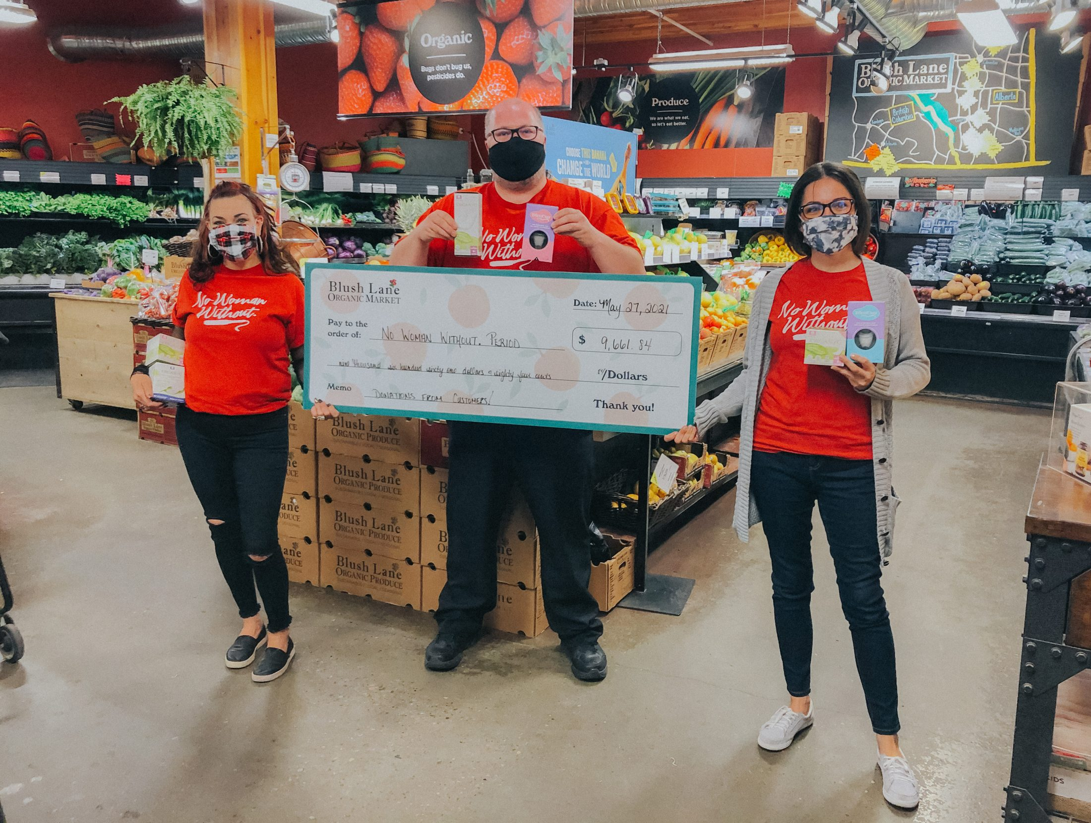 Three Blush Lane employees hold a cheque for the SPUD Period Poverty campaign
