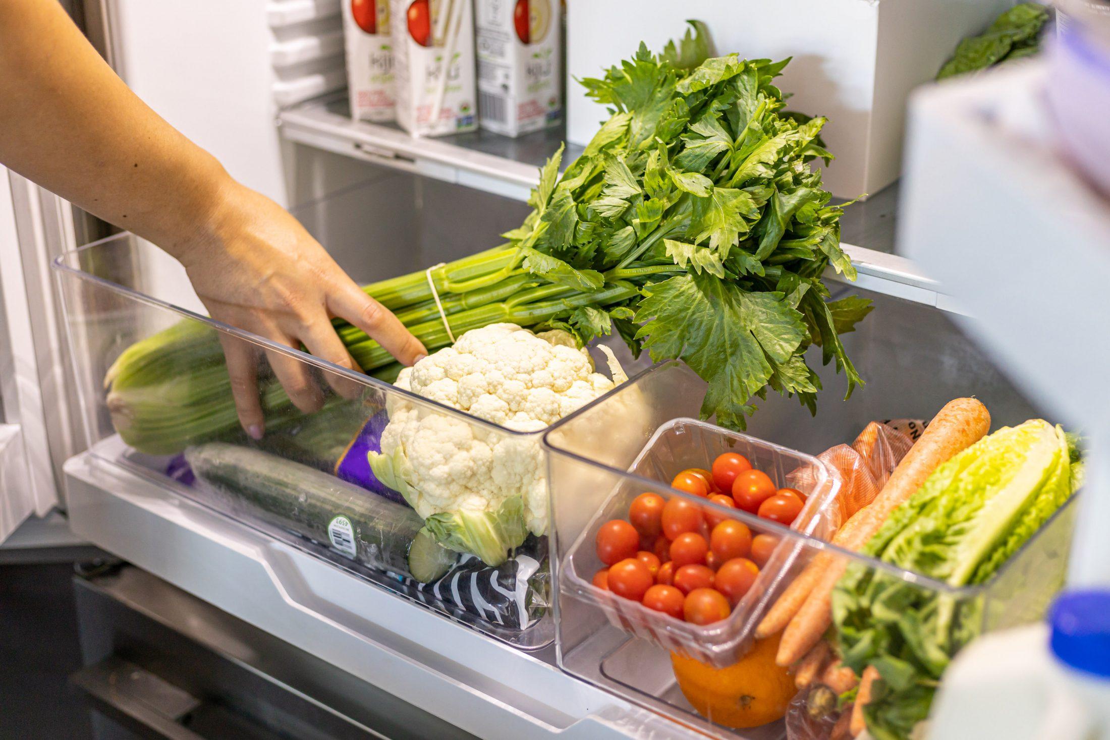 Woman grabs SPUD groceries from her fridge